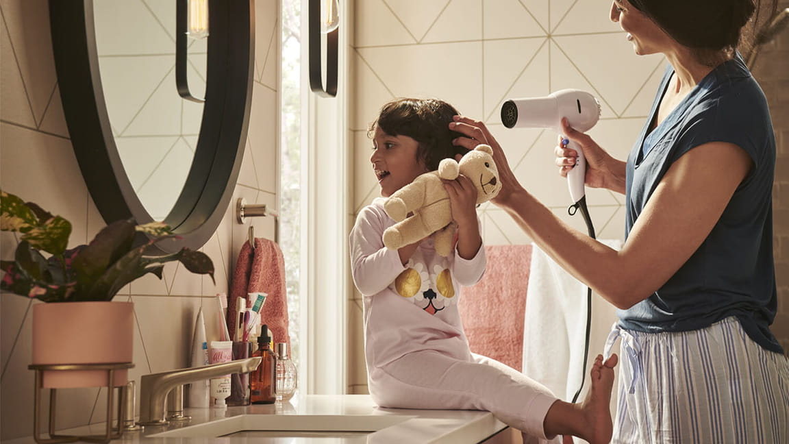 Girl on Sink with Adult Blowdrying Hair and American Standard Faucet