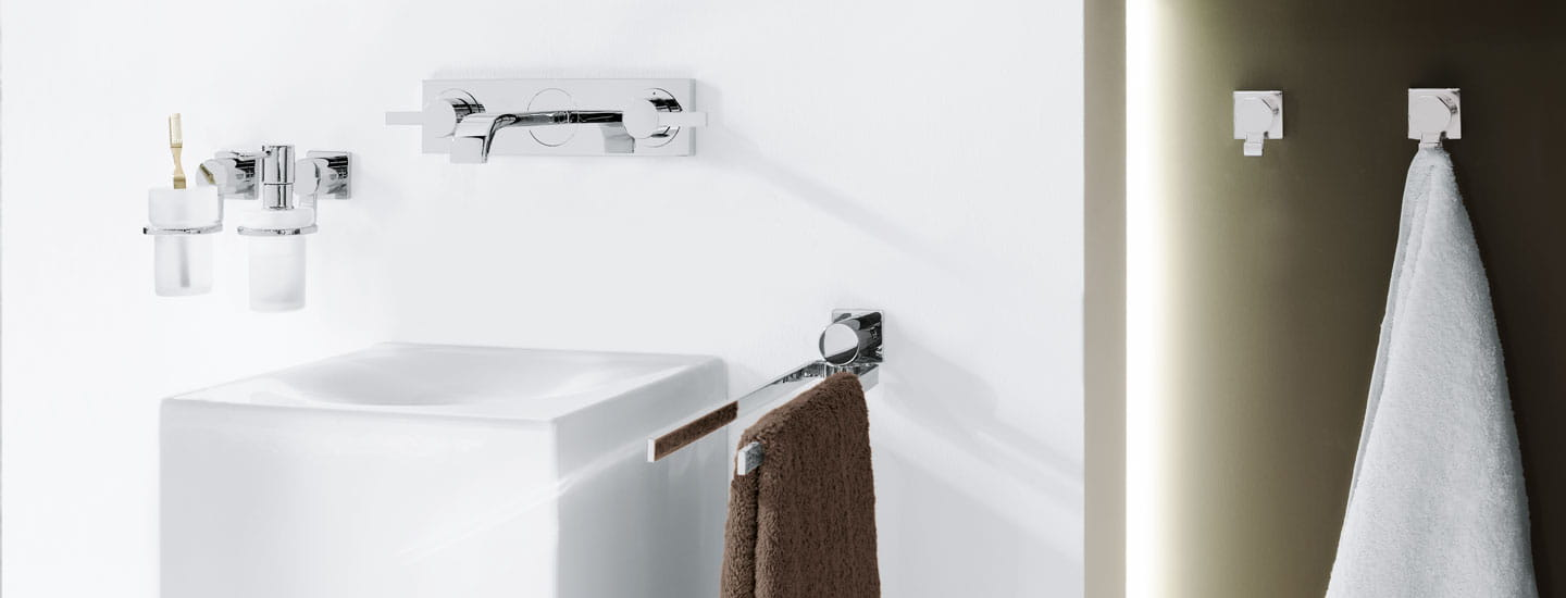 tooth brush holder, soap holder, white sink, faucet and two towel hangers