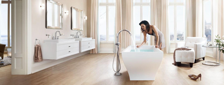 les femmes remplissant une baignoire en utilisant le robinet debout Grandera.