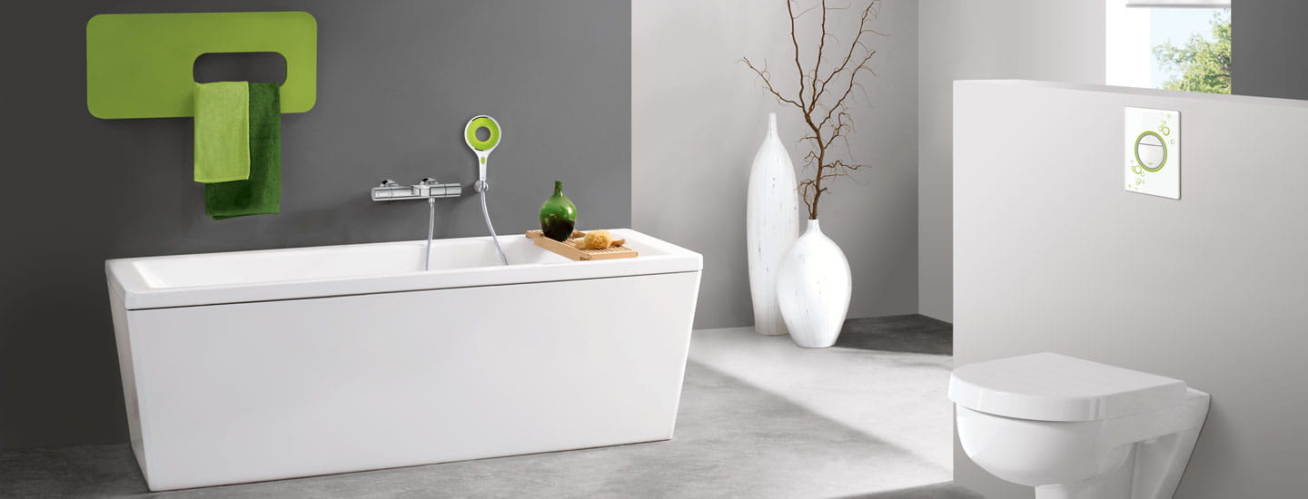 Grohe designer flush plate in a grey and green bathroom.