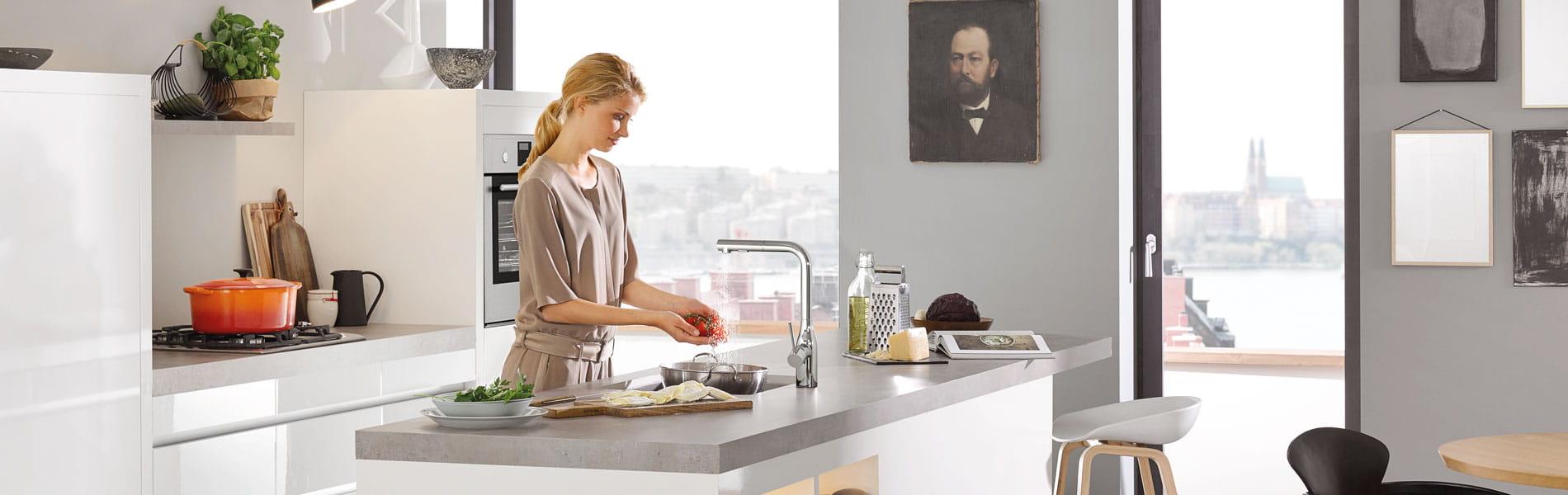Essence robinet de cuisine avec une femme lave une tomate