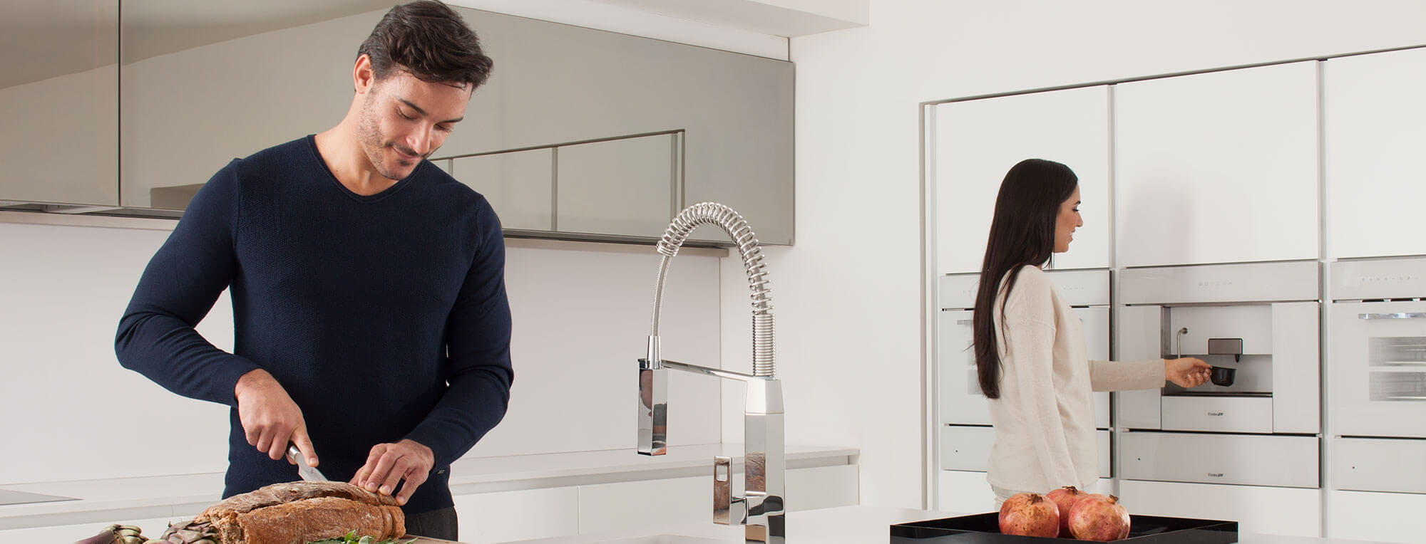 Eurocube kitchen faucet displayed in a kitchen with a women and man using it.