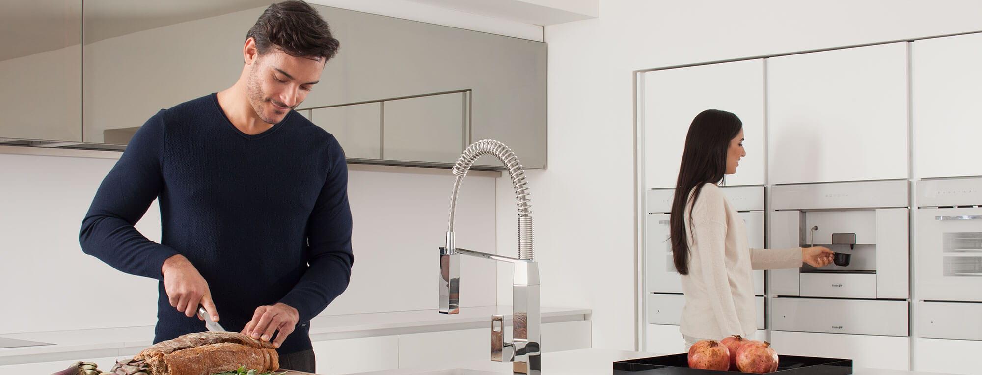 Robinet de cuisine Eurocube présenté dans une cuisine avec un homme et une femme l'utilisant.