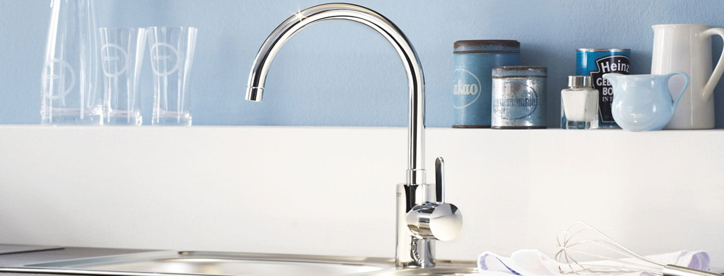 shiny kitchen faucet with glasses and containers on ledge behind