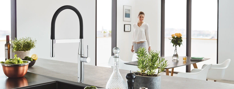GROHE Essence Kitchen Faucet in Kitchen Scene avec femme en arrière-plan