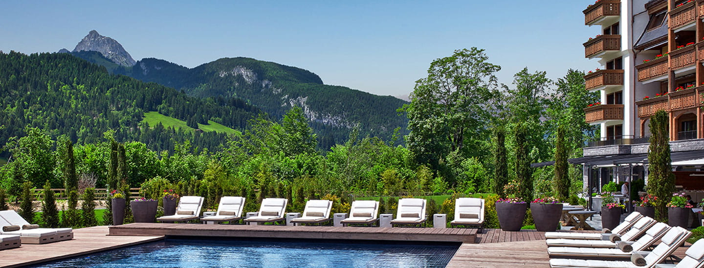Alpina hotel pool area with lounge chairs and mountains in background