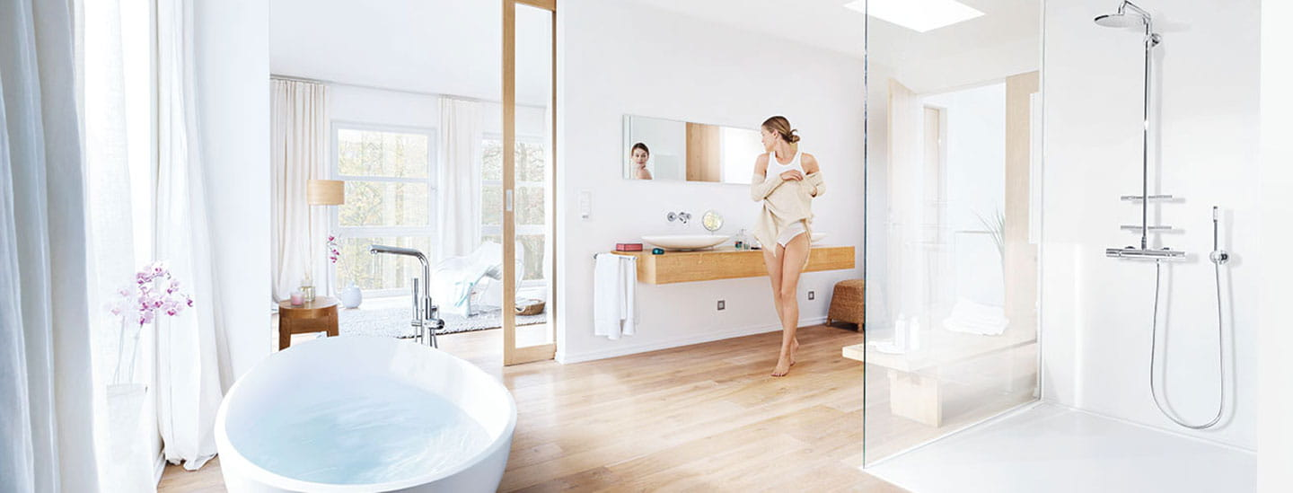 open bathroom with filled bathtub and woman looking in mirror