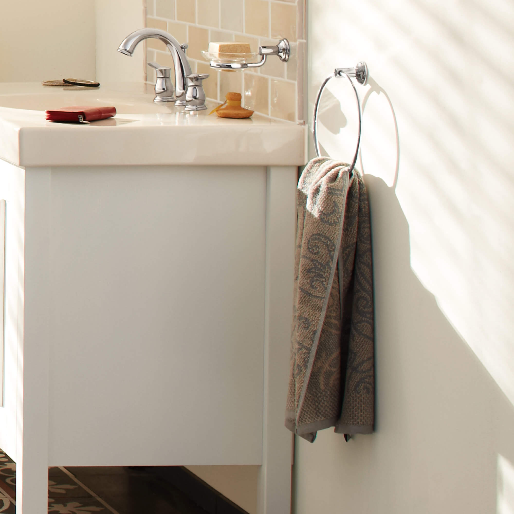 Essentials Authentic accessory towel ring next to a bathroom sink cabinet.