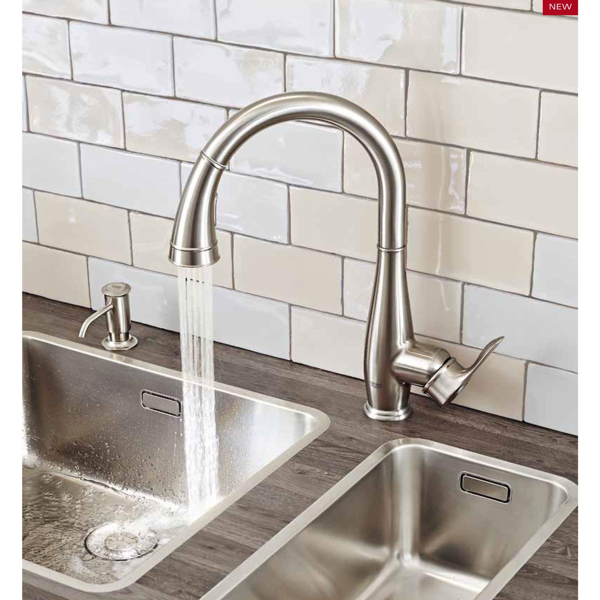 robinet avec l'eau courante et le fond blanc de tuile
