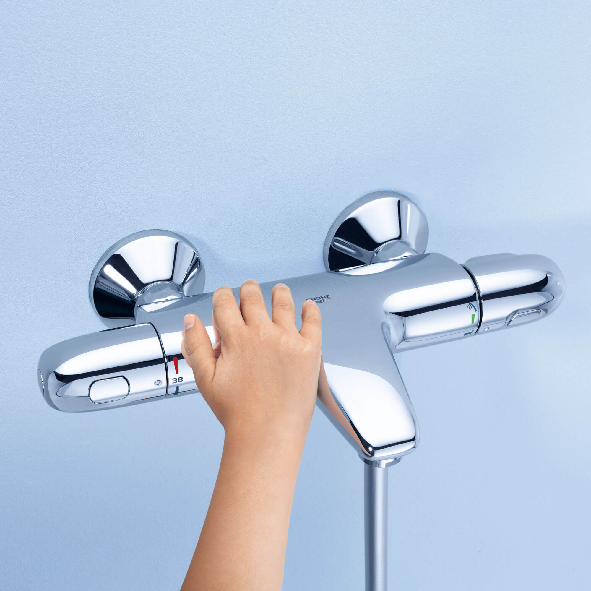 A child's hand reaching for a thermostatic knob.