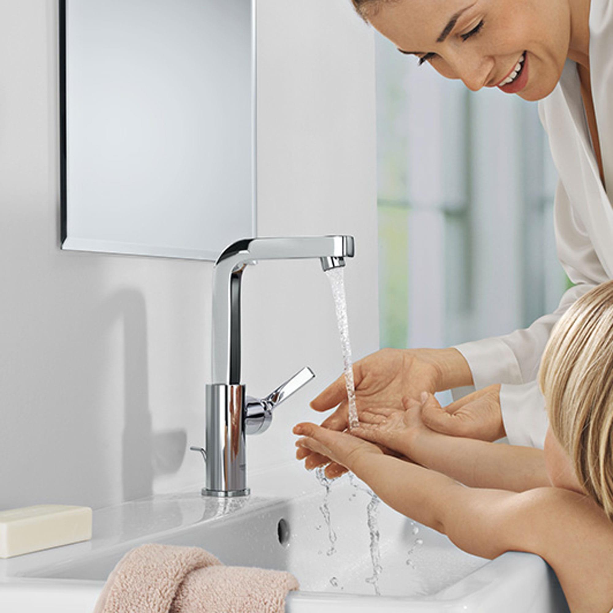 Une femme la lavent et les mains de son enfant sous un robinet grohe.
