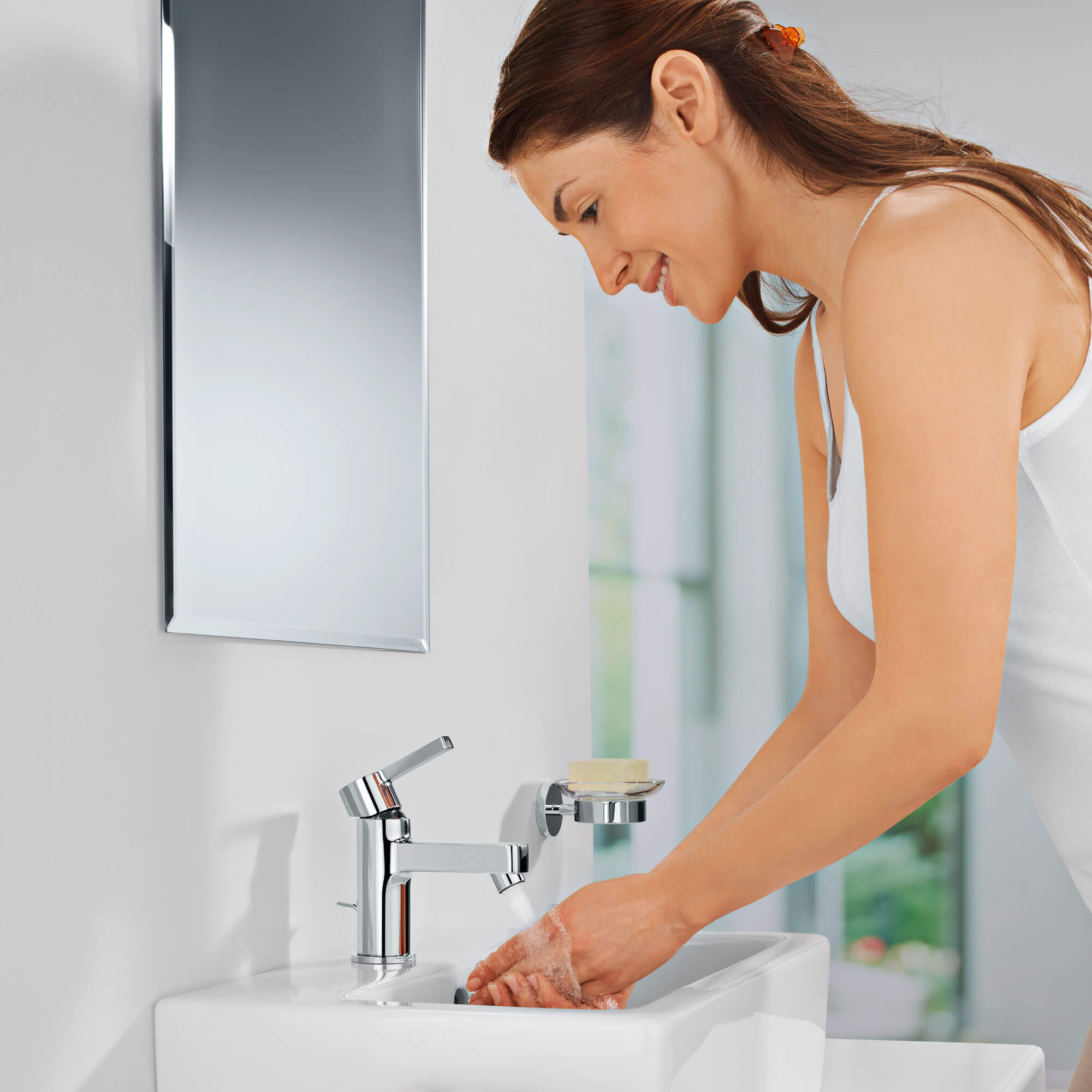 A women washing her hands under a grohe faucet.