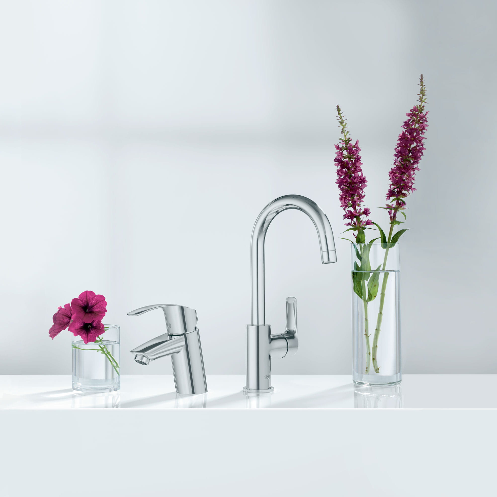 A pair of Grohe faucets next to vases filled with flowers.