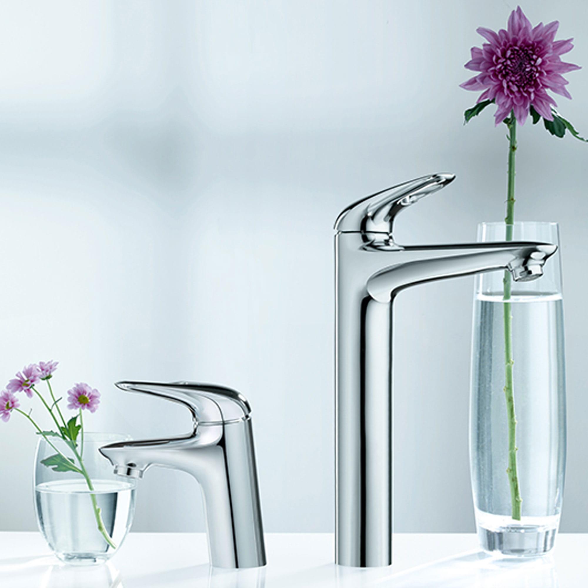 Une paire de robinets Grohe à côté de vases remplis de fleurs.