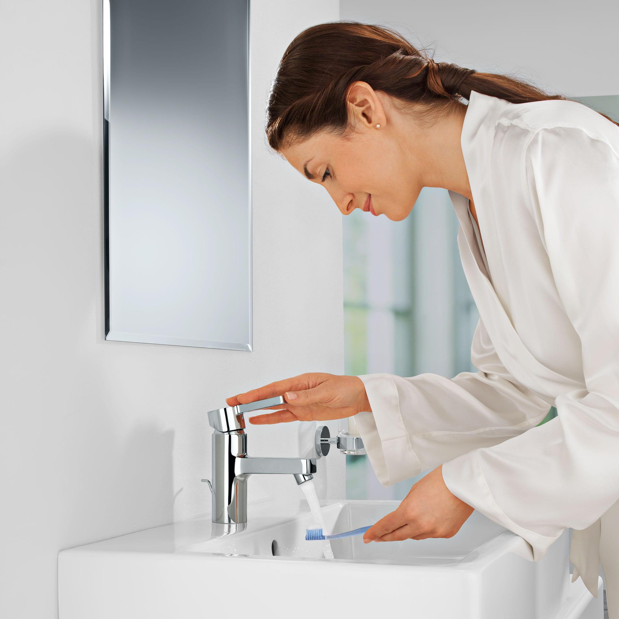 Une femme se lave les mains sous un robinet grohe.