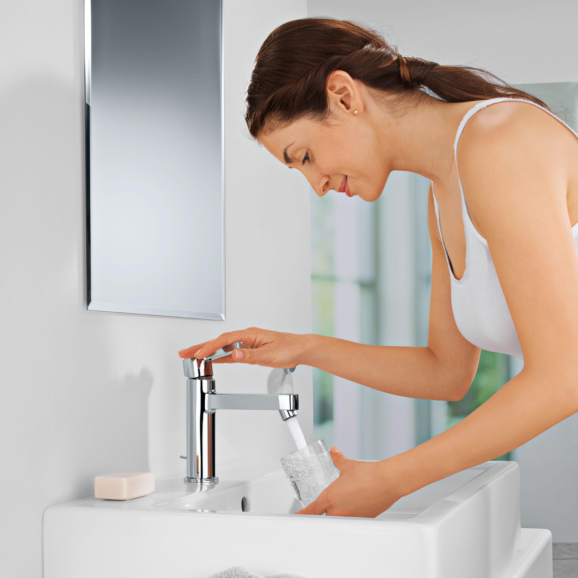 Une femme remplissant un verre sous un robinet grohe.