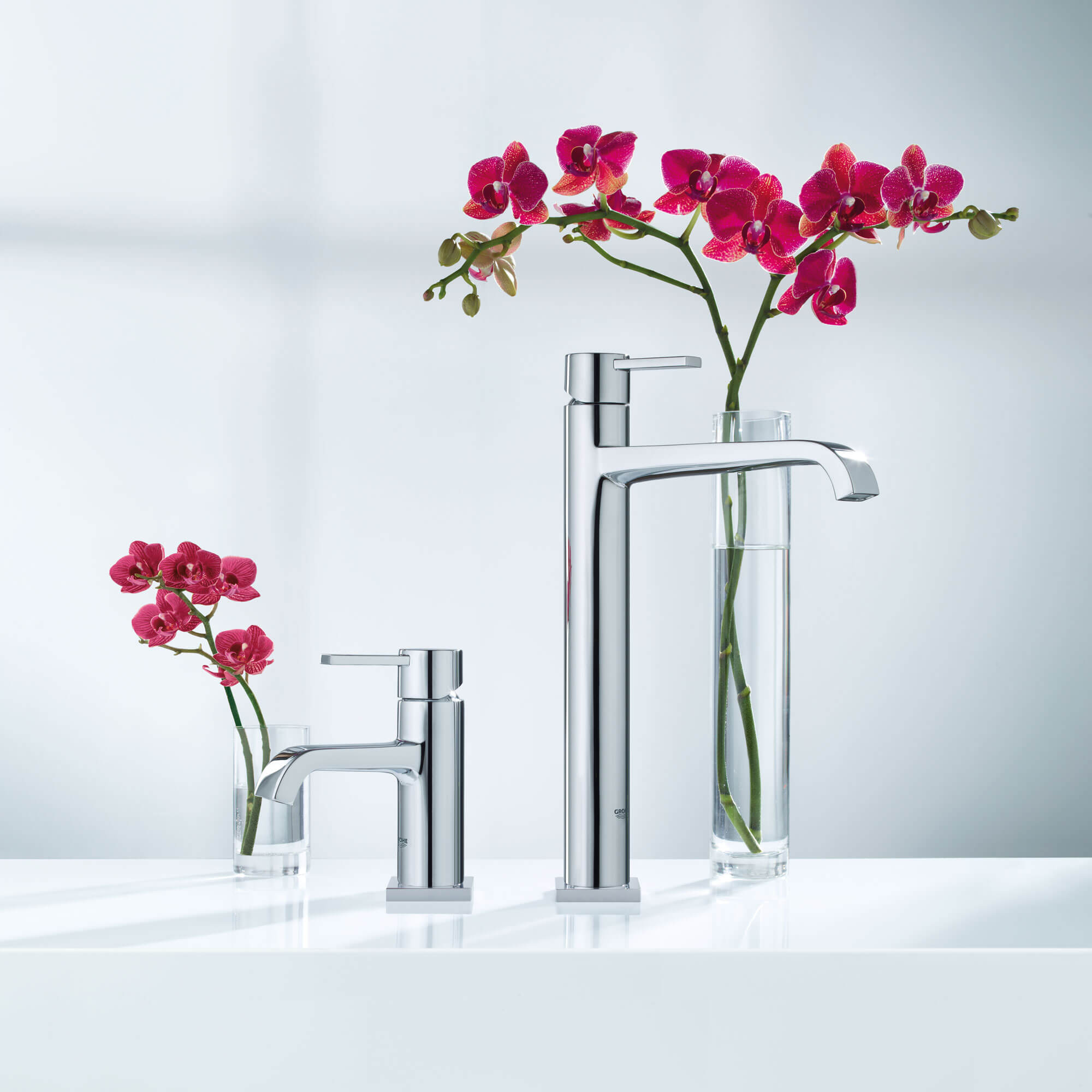 Two Grohe faucets next to two glasses filled with flowers.