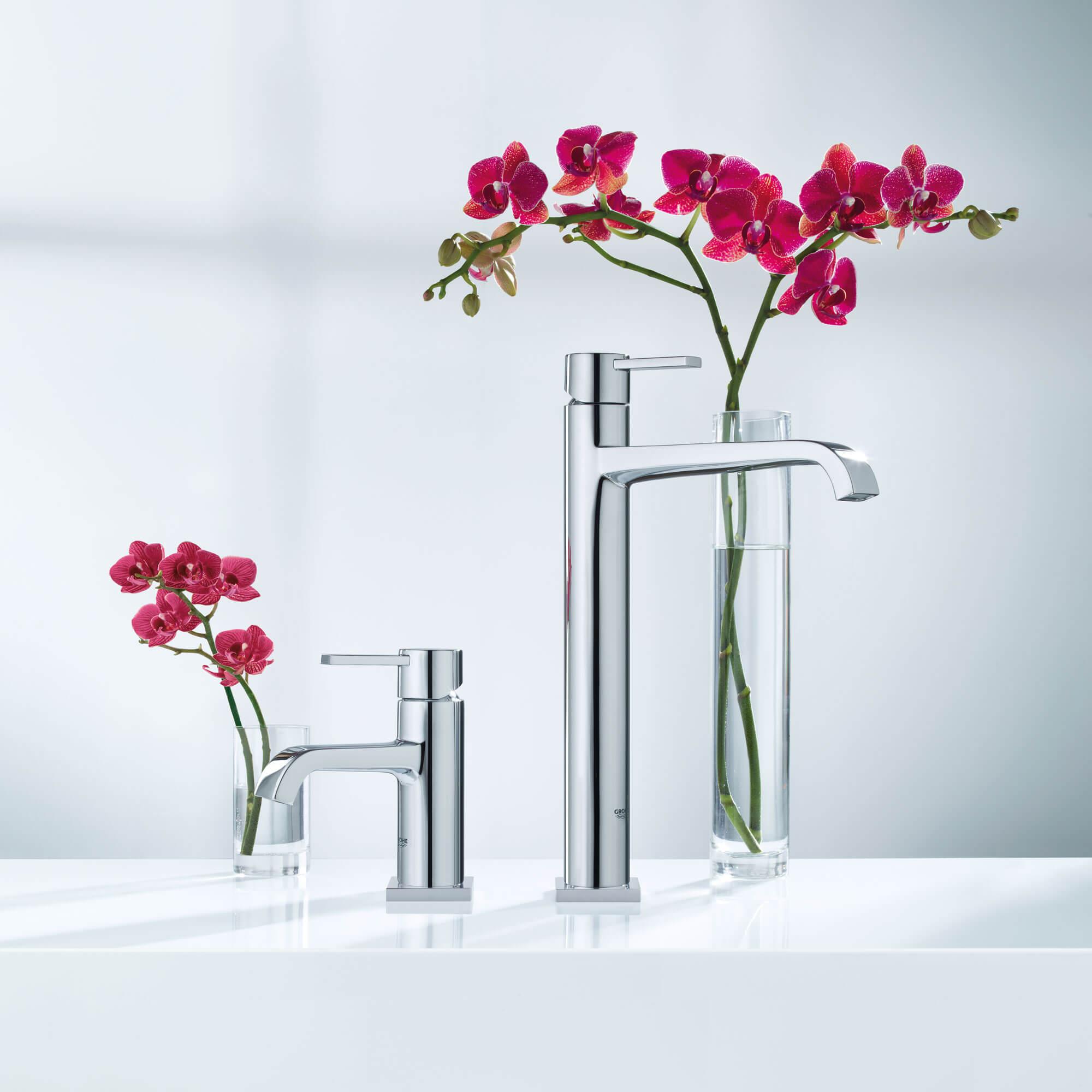 Deux robinets Grohe à côté de deux verres remplis de fleurs.
