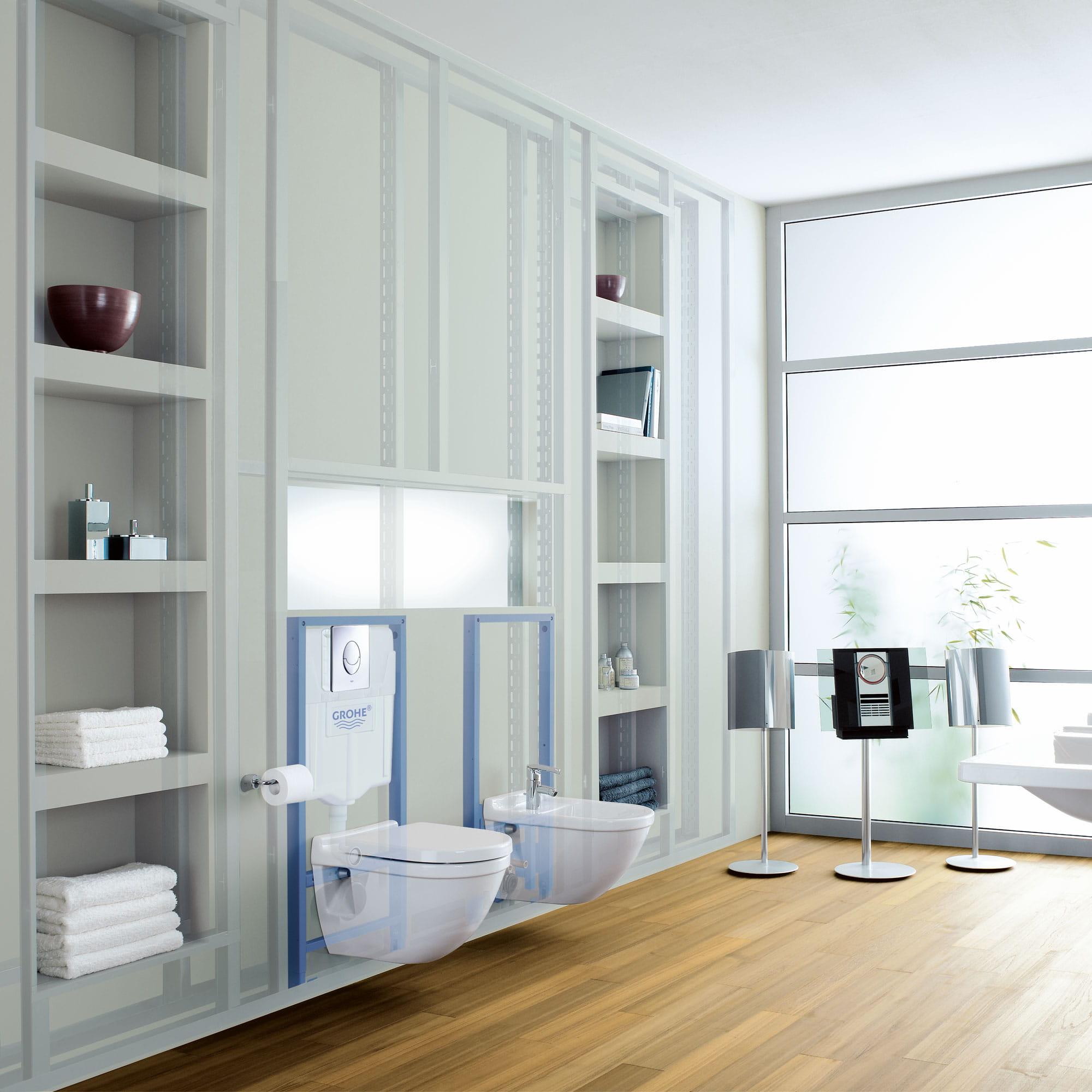 Salle de bain avec deux toilettes accrochées au mur.