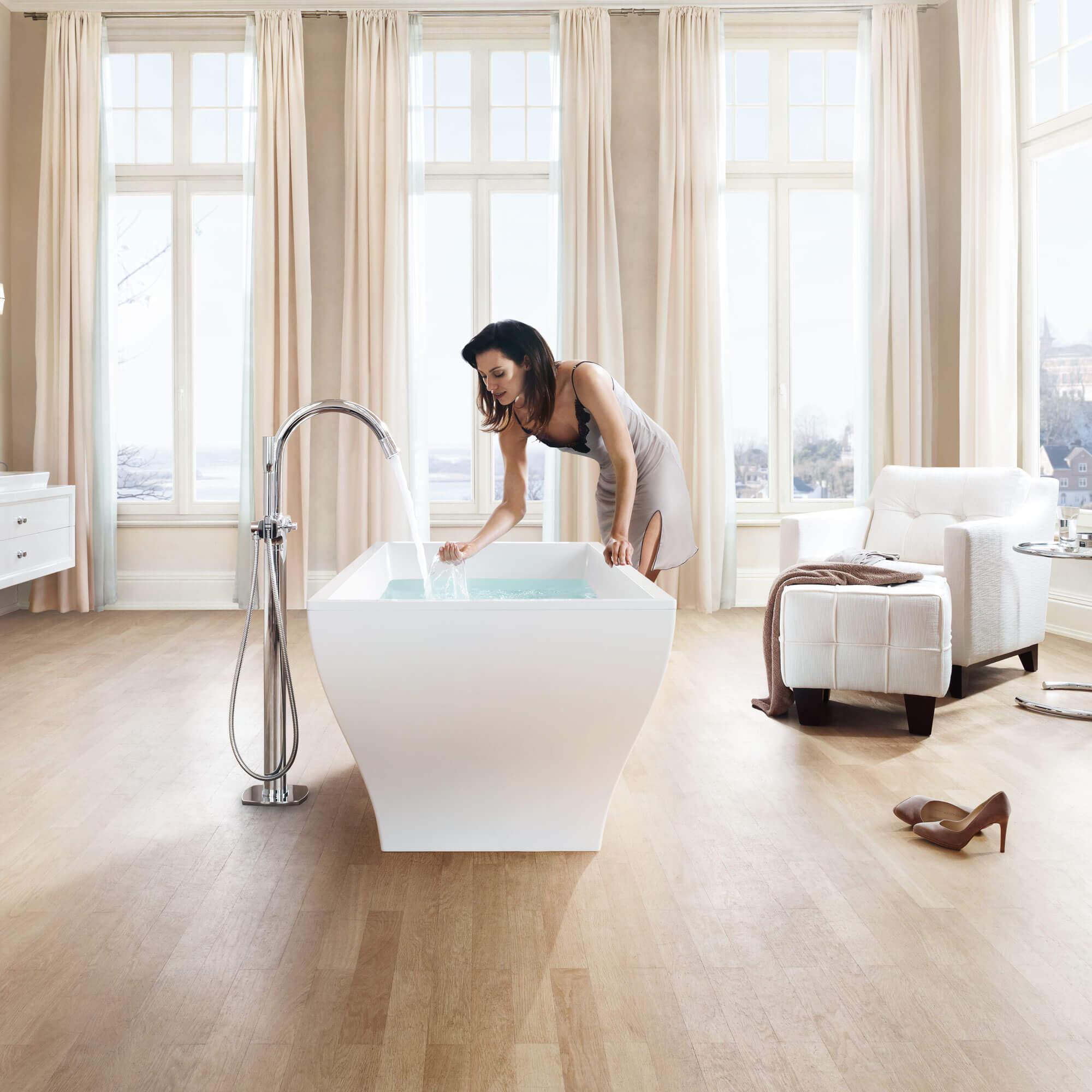 Thermostats GROHE - femme touchant l'eau dans la baignoire