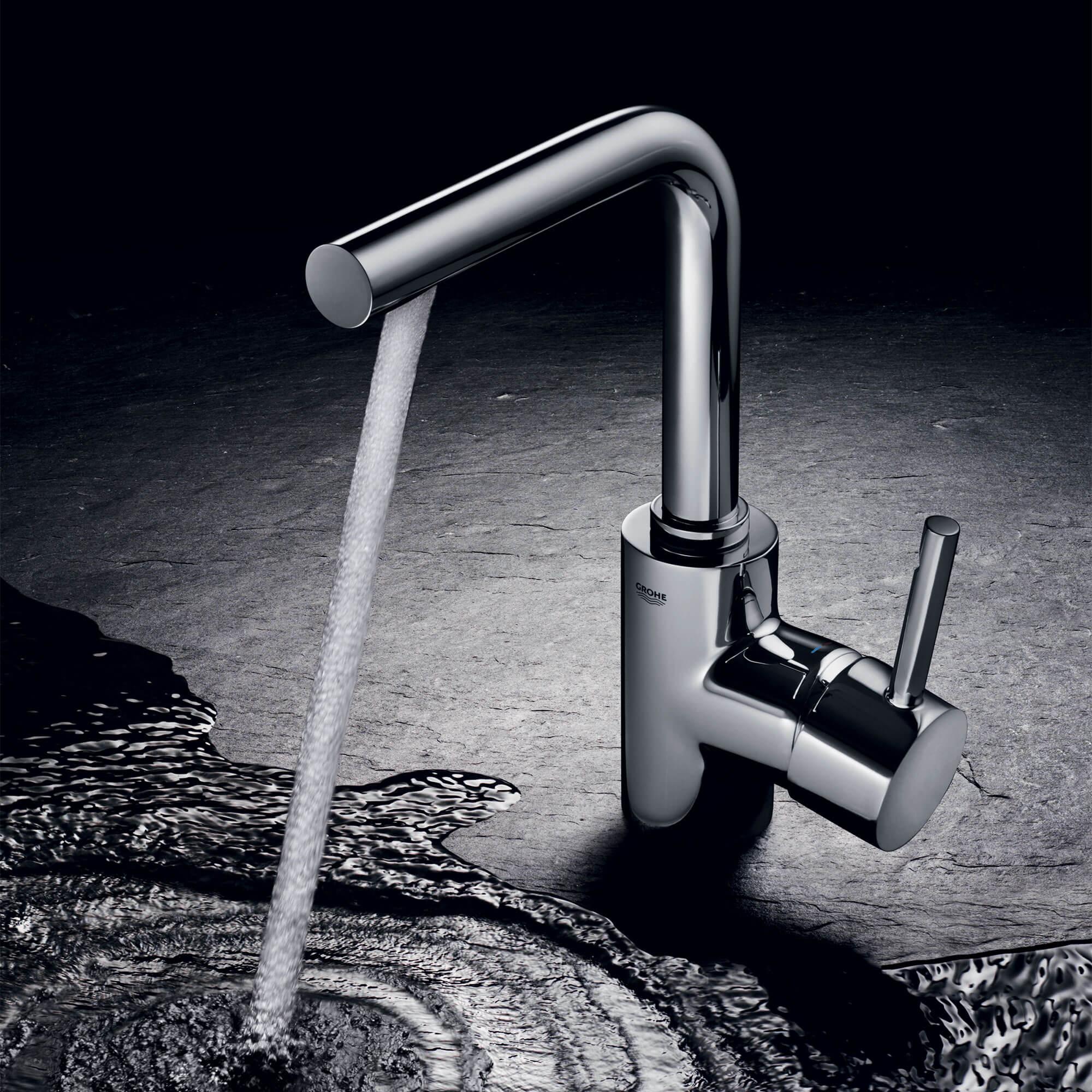 Le robinet de salle de bain Essence pulvérise de l'eau dans une flaque d'eau.