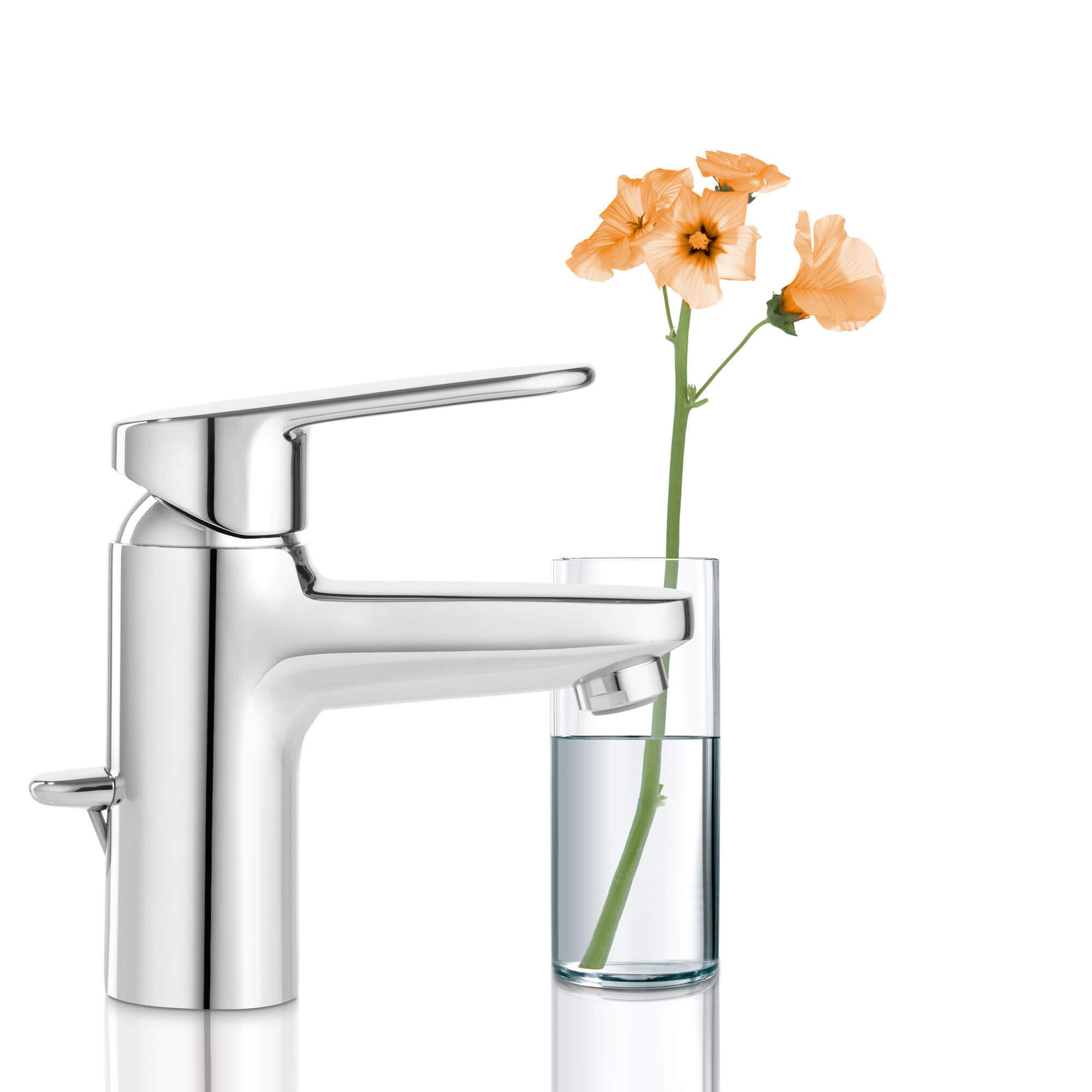 Robinet de salle de bain Europlus à côté d'un verre rempli de fleurs.