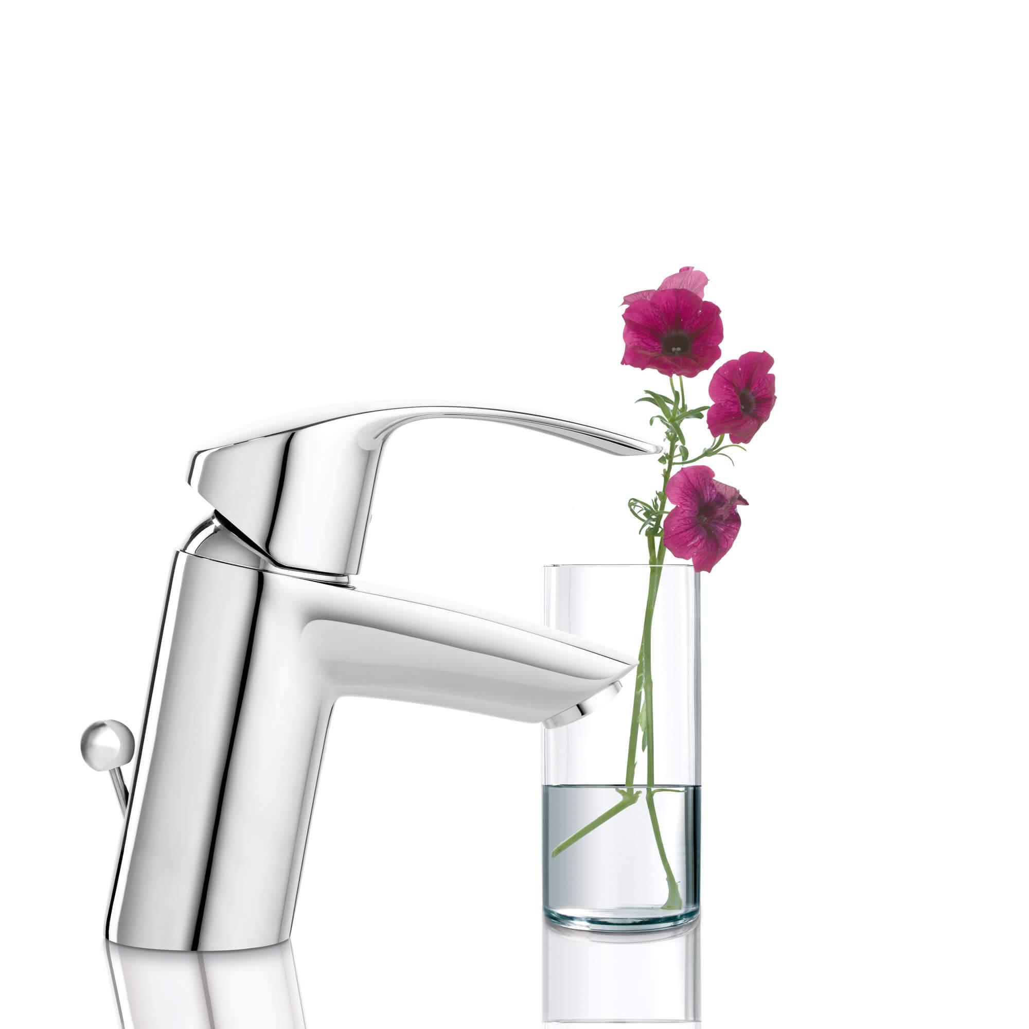 Le robinet Eurosmart est illustré à côté d'un verre rempli de fleurs.