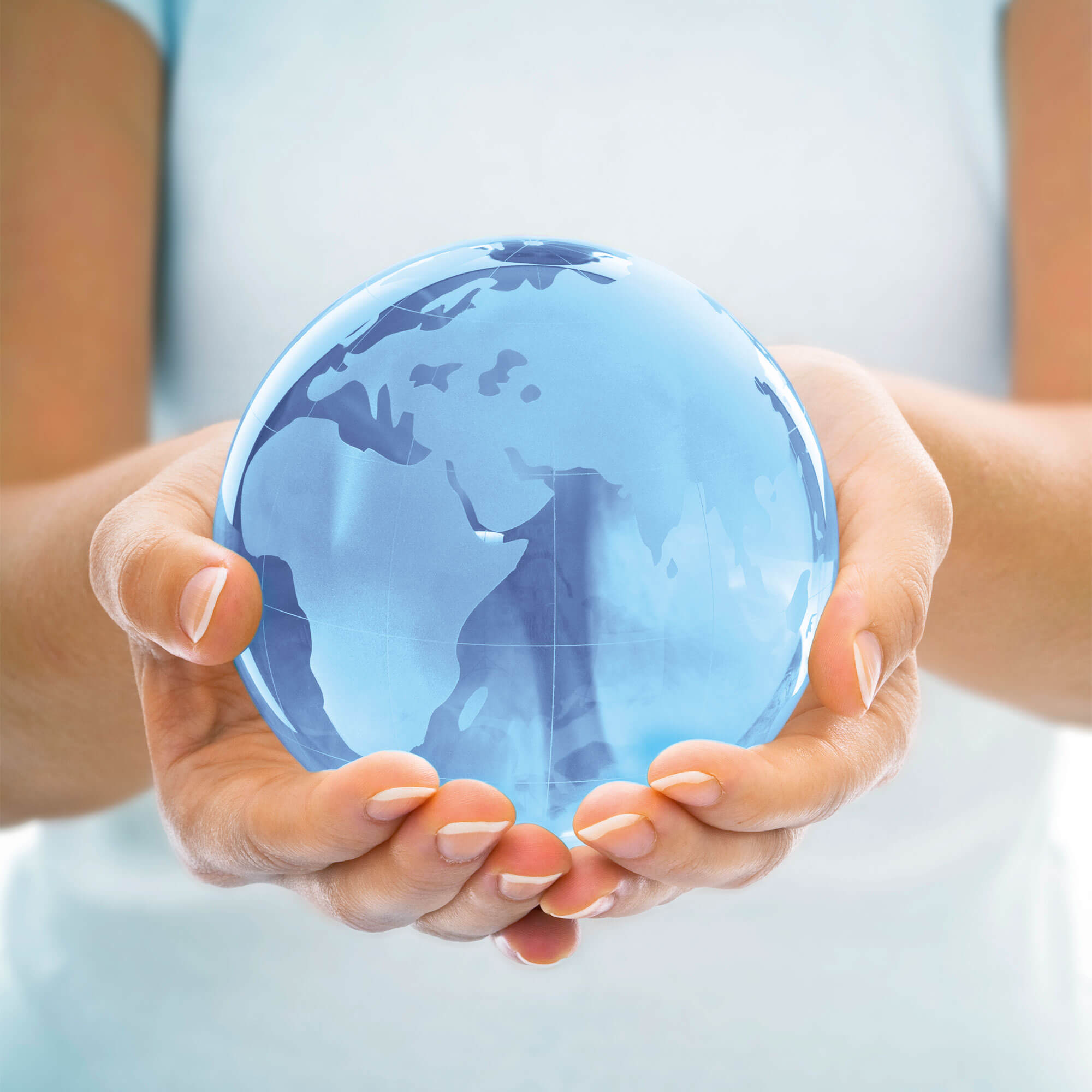 Person holding a blue glass globe in hands.