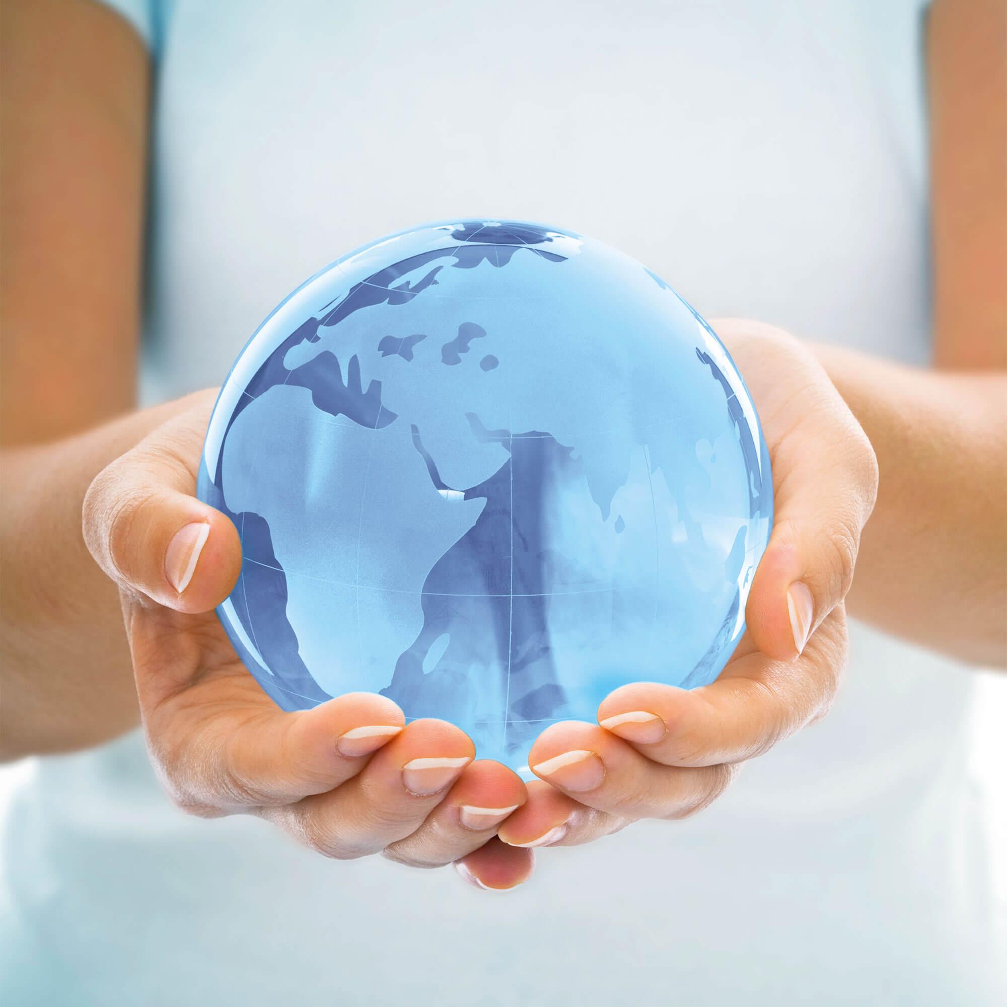 Personne tenant un globe en verre bleu dans les mains.