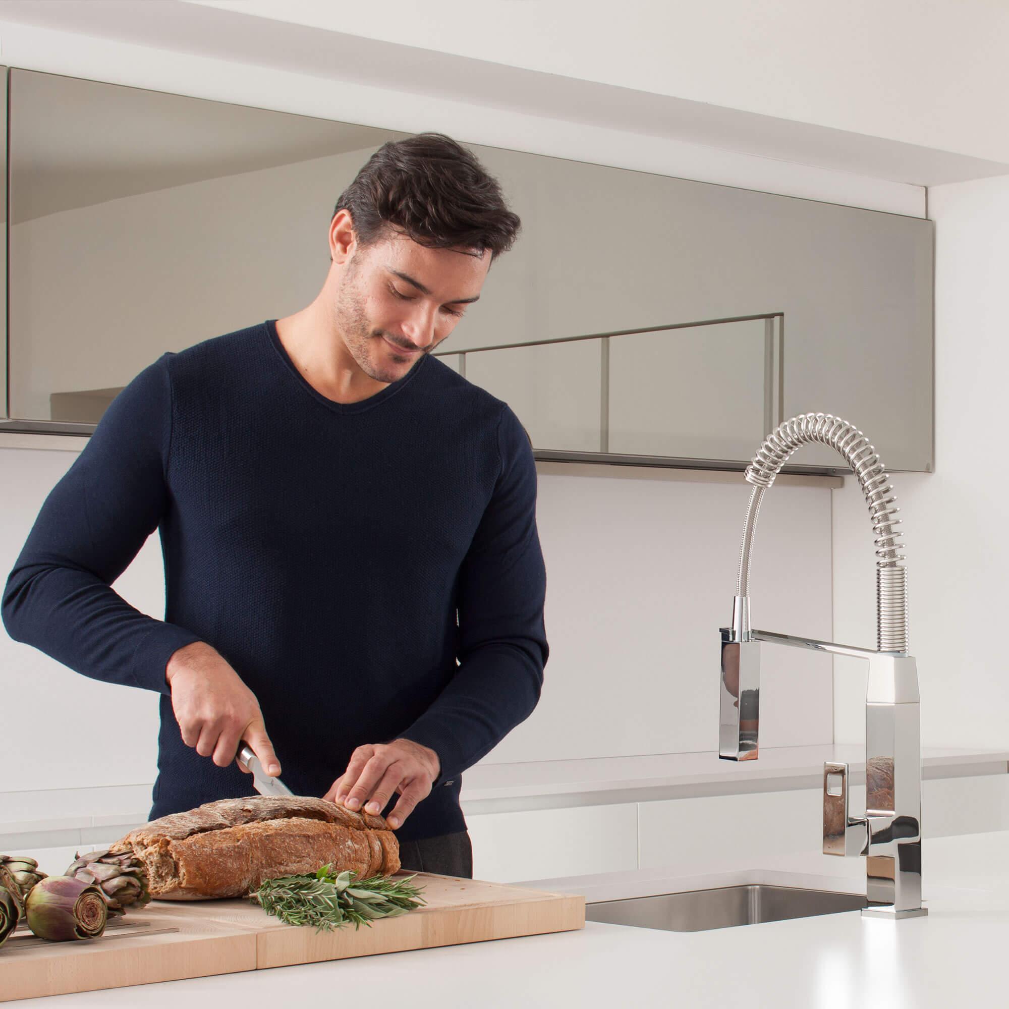 Eurocube Robinet de cuisine devant un homme coupant le pain sur la planche à découper