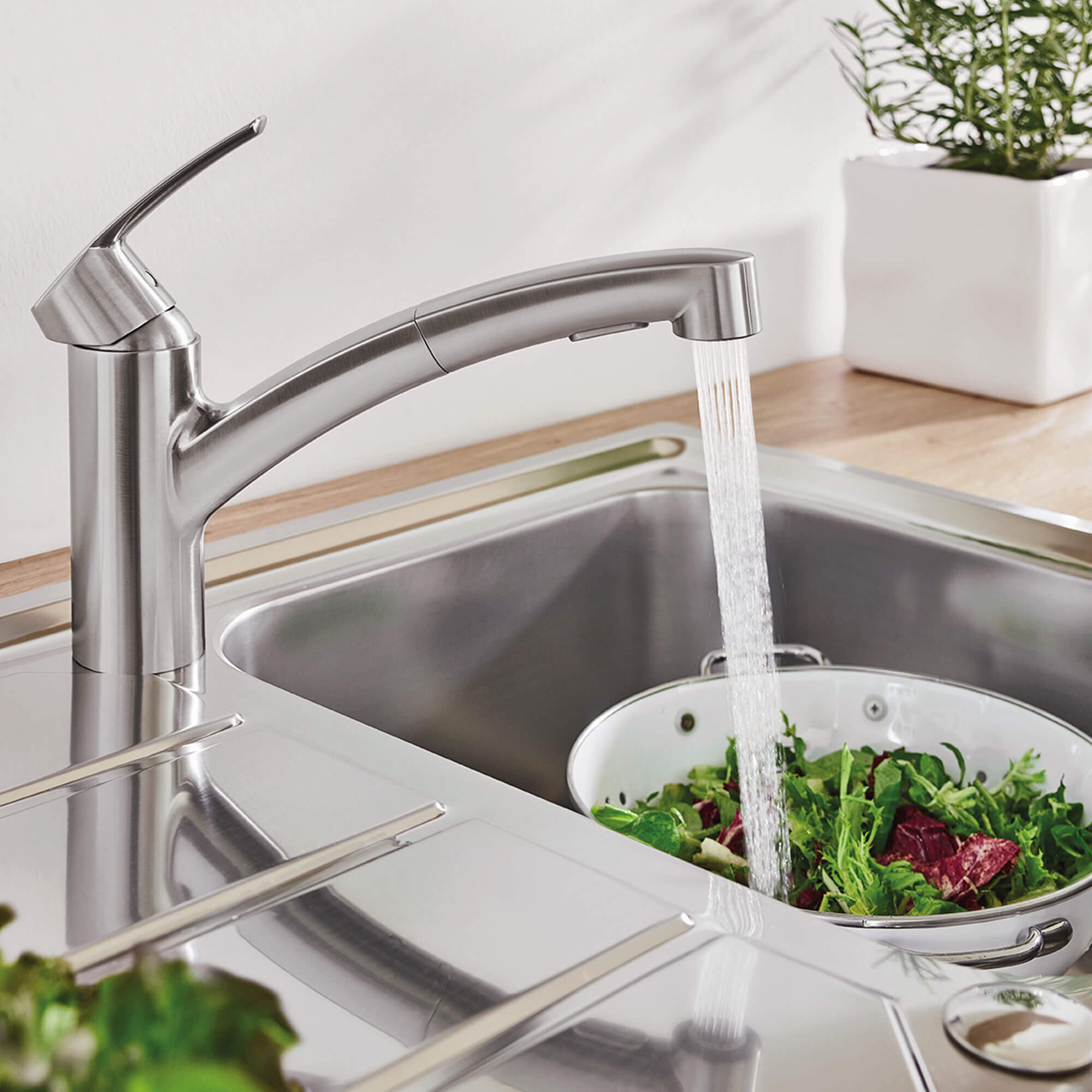Eurosmart kitchen faucet spraying water on a bowl of lettuce.