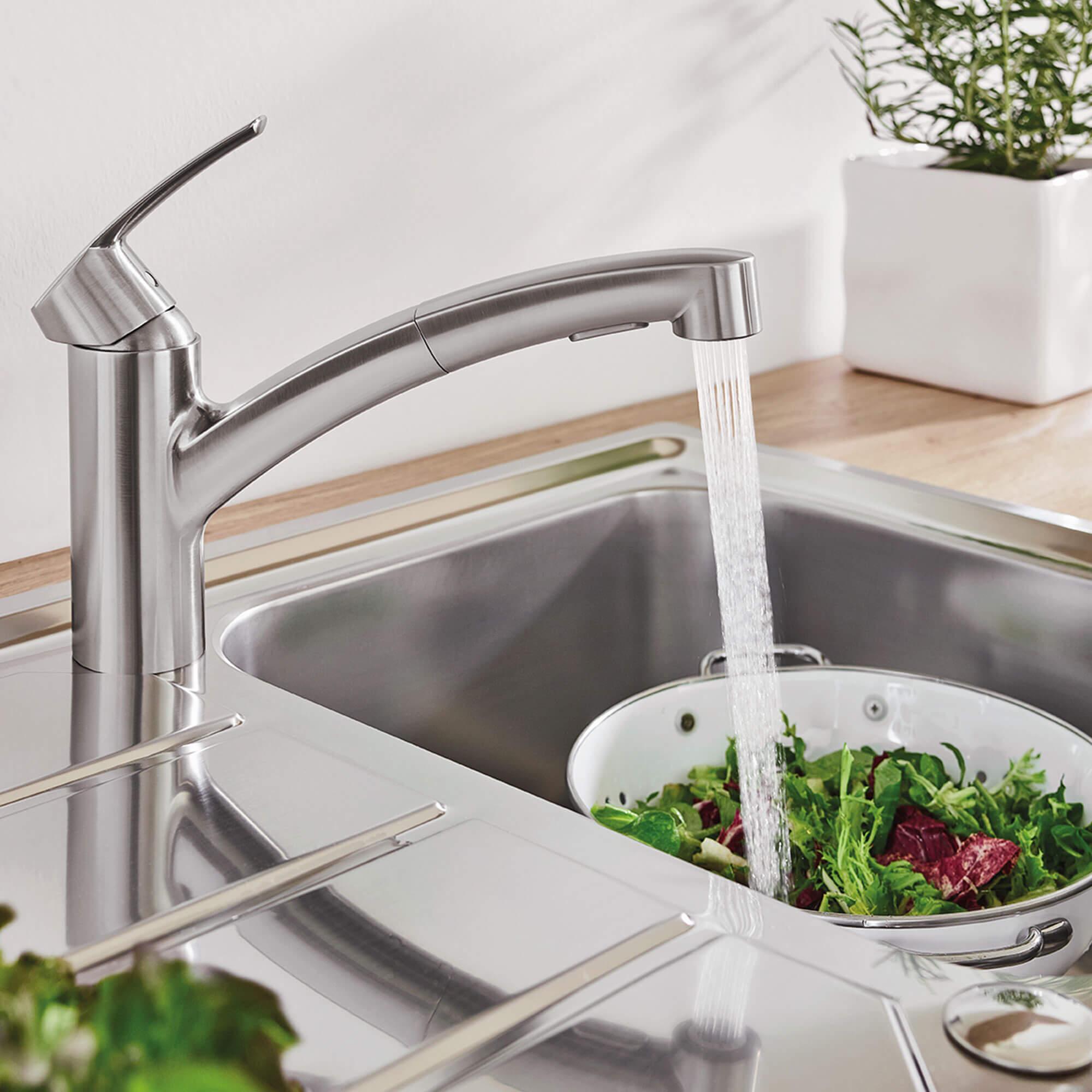Le robinet de cuisine Eurosmart pulvérise de l'eau sur un bol de laitue.