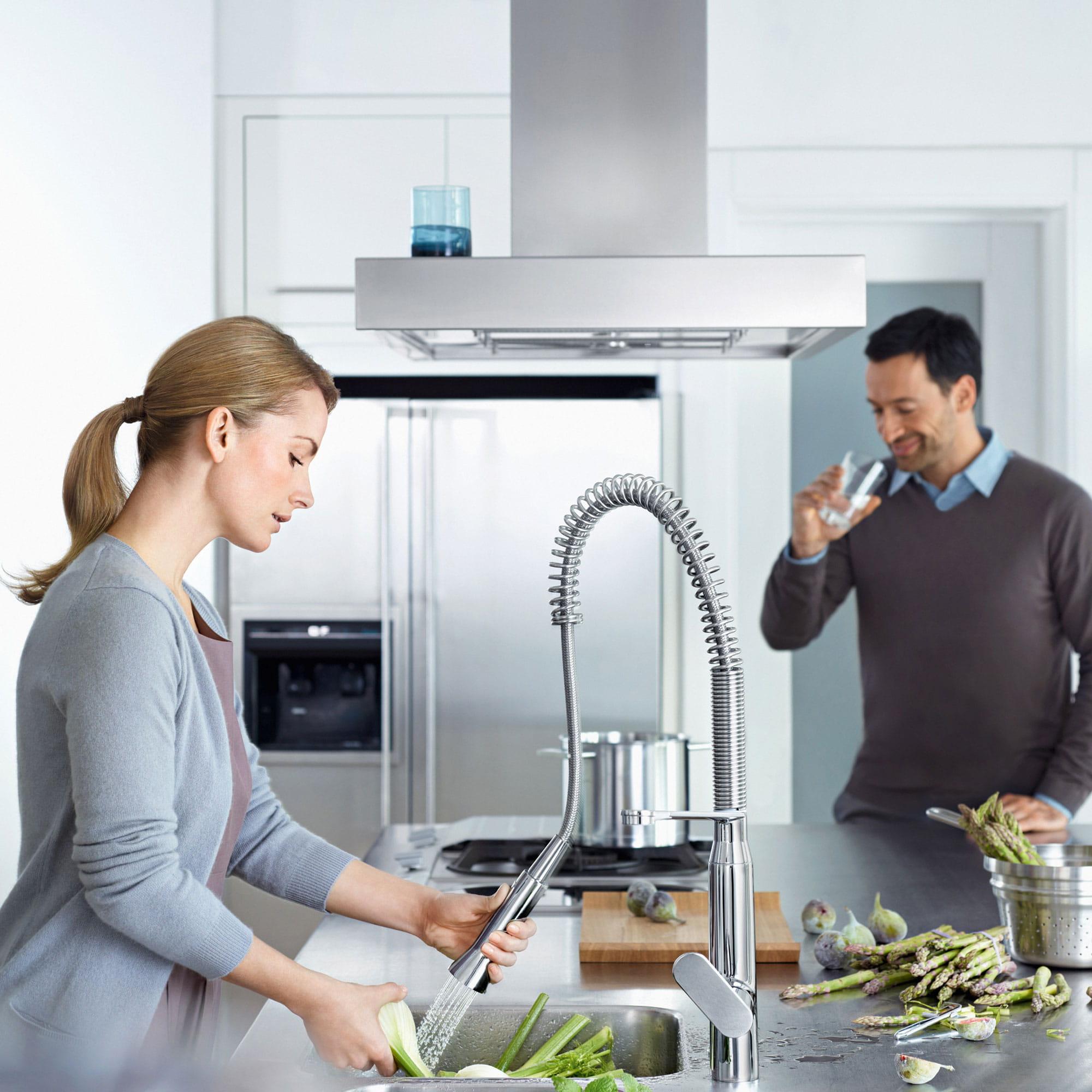 les gens dans la cuisine tout en lavant les légumes