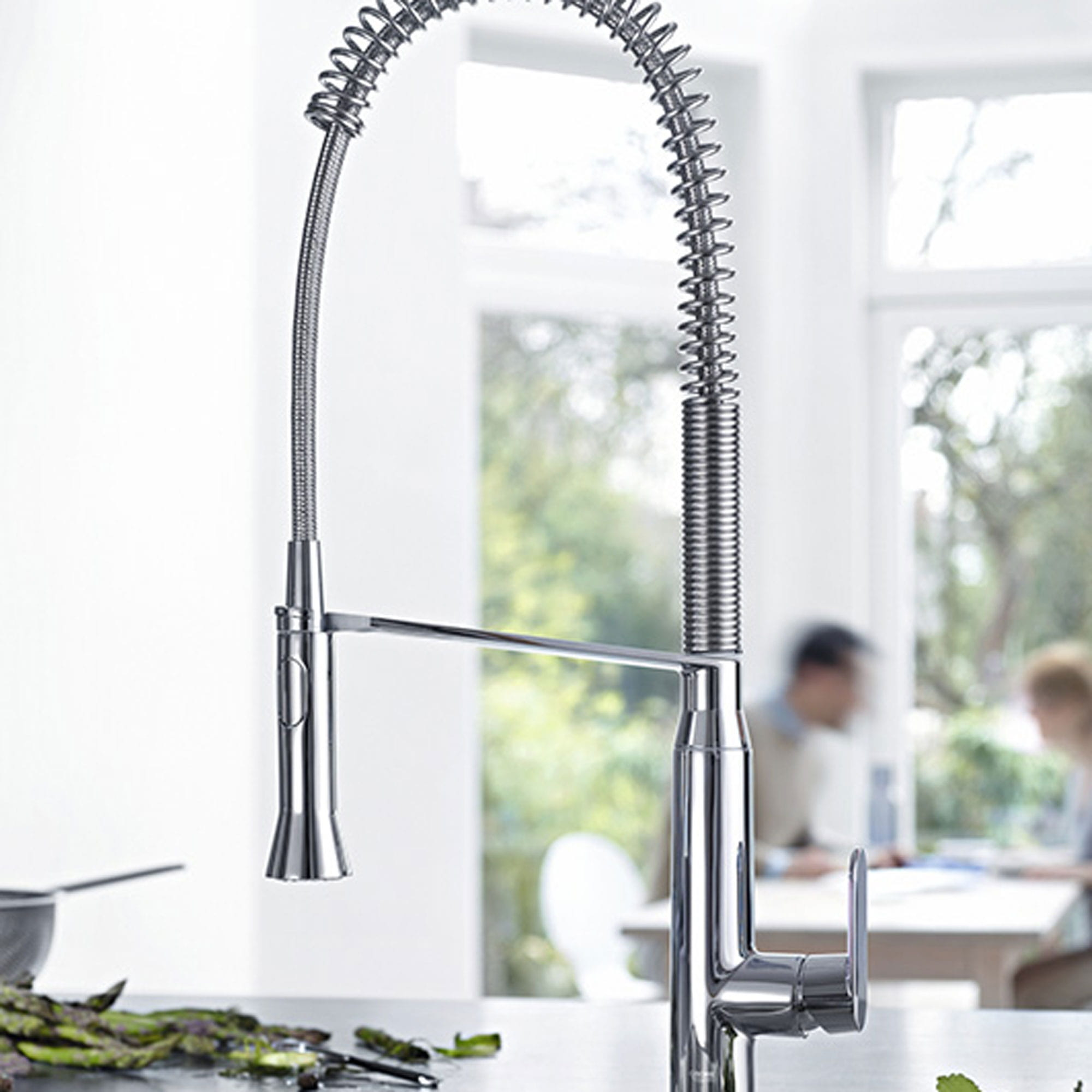 kitchen faucet with two people in blurred background