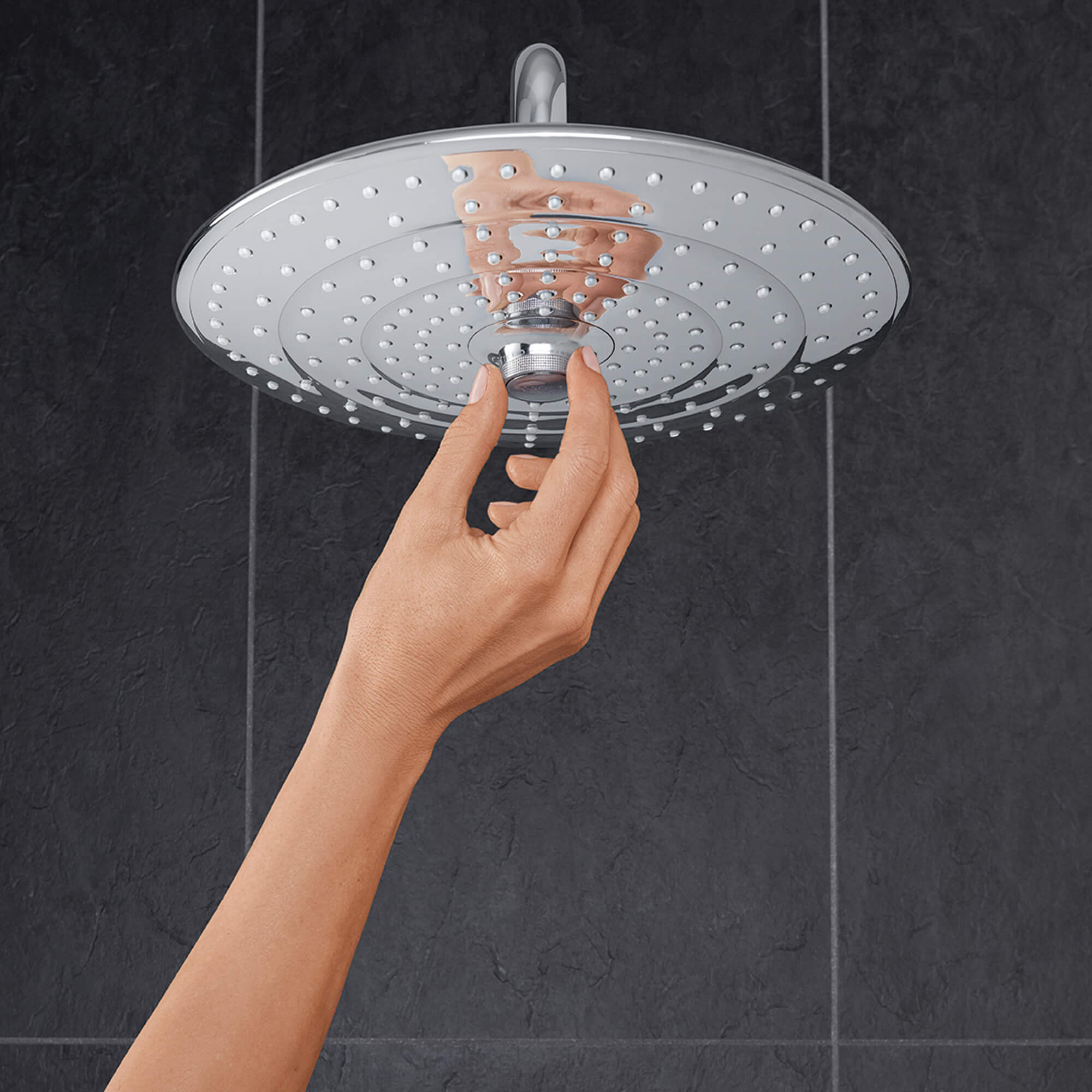 Hand adjusting centerpiece of Euphoria shower head