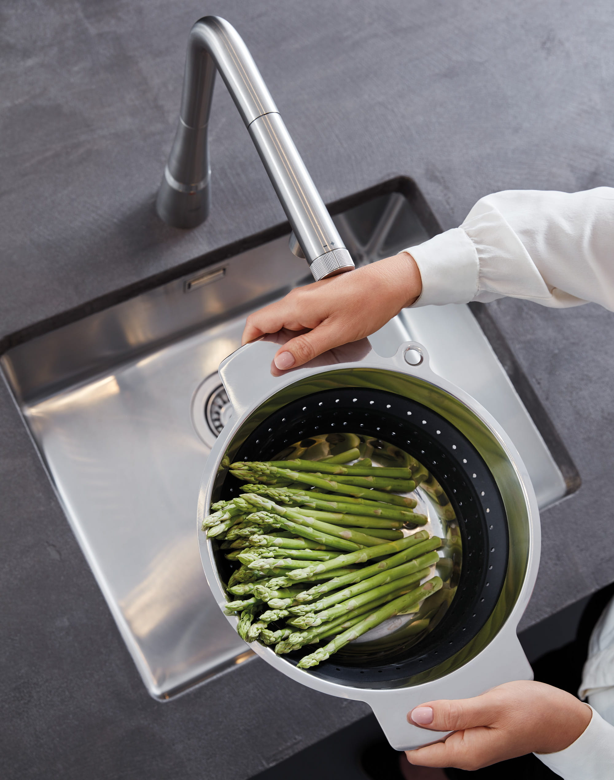 Touch faucet in use washing asparagus in the kitchen