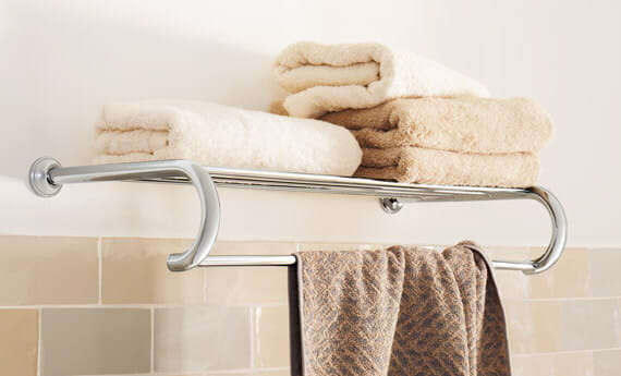 Essentials Authentic accessory towel rack with folded towels on top of it.