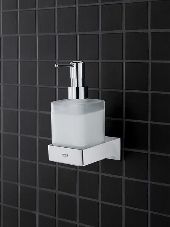 Distributeur de savon de cube de sélection devant le fond noir de tuile