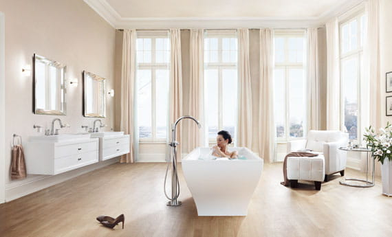 Women taking a bath next to a standing Grandera faucet.