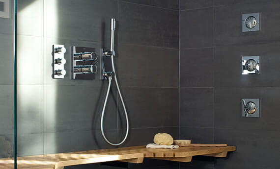gray shower with wall jet spray, handshower, wall controls, and wooden bench