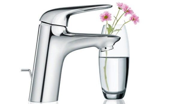 Eurostyle bathroom faucet next to a cup of water with flowers.
