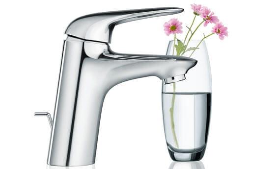 Robinet de salle de bains Eurostyle à côté d'une tasse d'eau avec des fleurs.