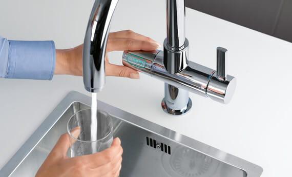 GROHE Blue Pure robinet de cuisine avec la personne remplissant un verre d'eau