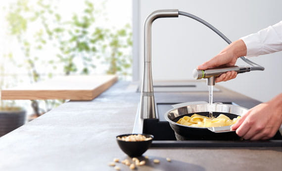 Femme utilisant le robinet de cuisine de SmartControl pour laver la nourriture